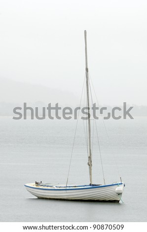 White sailing dinghy with blue trim moored in rainstorm. Tasmania, Australia - stock photo