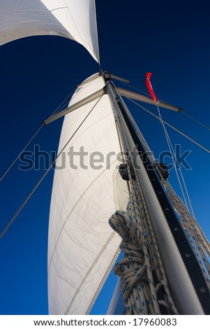 white sails against blue sky - stock photo