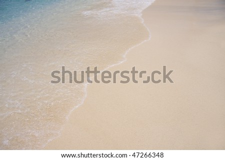 White sand of tropical shoreline with wave rolling up the shore. - stock photo