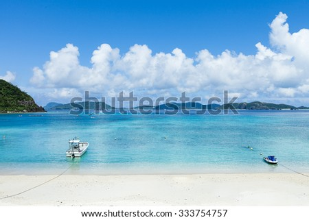 White sand tropical beach and clear blue water with boats, Kerama Islands National Park, Okinawa, Japan - stock photo