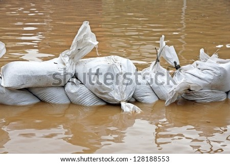 White sandbags for flood defense and brown water - stock photo