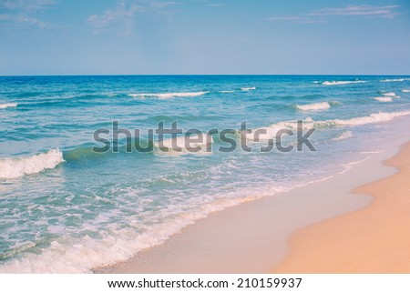 White sandy beach, turquoise ocean and waves - stock photo