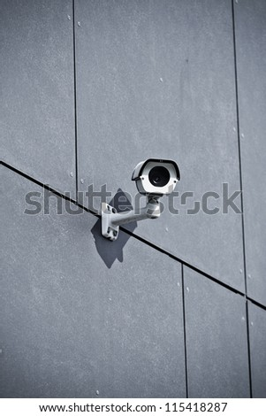 White security camera on office building, safety system - stock photo