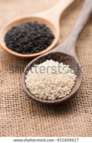 White sesame and black sesame seed on wooden spoon - stock photo