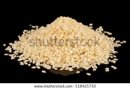 White sesame seeds heap on black reflective surface, isolated on black background - stock photo