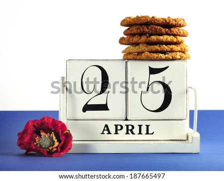 White shabby chic vintage style block calendar for Anzac Day, April 25, with traditional Anzac biscuits on white background with remembrance red poppy - stock photo