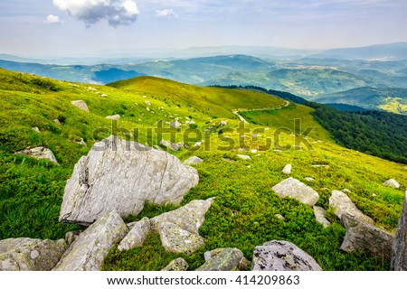 white sharp boulders on the grassy meadow with some dandelions on the edge of high mountain range - stock photo