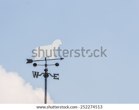 white sheep rooster weather vane in blue sky. - stock photo