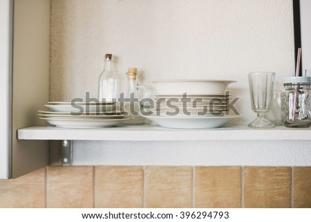 White shelf in kitchen with plates, glasses and jars - stock photo