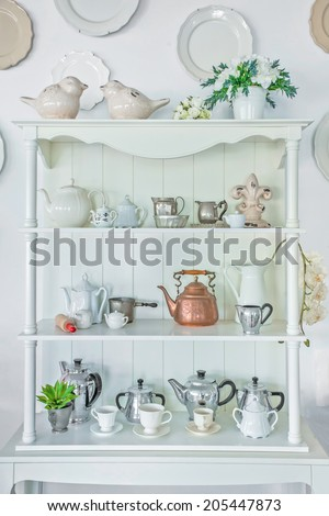 White shelf with vintage porcelain tableware - stock photo