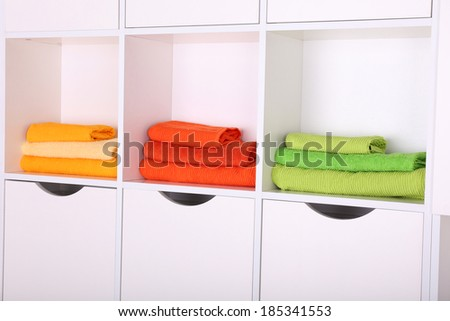 White shelves with colored towels close up - stock photo