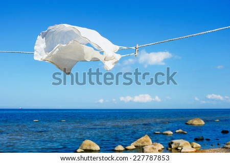 White shirt hanging on a rope on the beach - stock photo