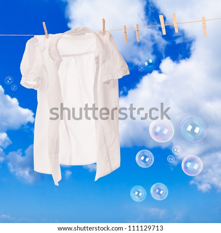 White shirt hanging on washing line with soap bubbles against a blue sky - stock photo