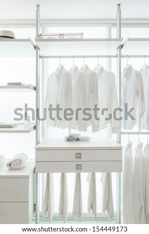 white shirts hanging on white built-in cloths racks, with drawers and other accessories - stock photo