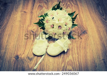 White shoes and white bouquet on a wooden floor - stock photo