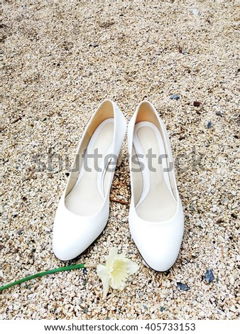 White shoes on a yellow background of small stones. Shoes bride with flowers. White shoes with yellow narcissus on the rocks . - stock photo