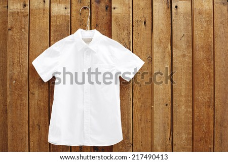 White short sleeved shirt hanging against wooden wall  - stock photo