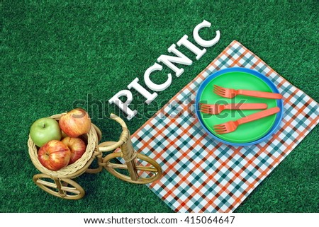 White Sign Picnic On Lawn, Plastic Plates, Forks And Wicker Bike Basket With Apples, Top View - stock photo
