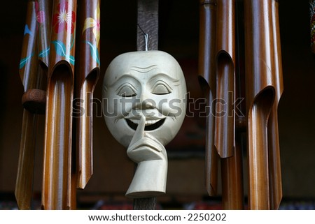 White smiling face mask surrounded by bamboo wind chimes - stock photo