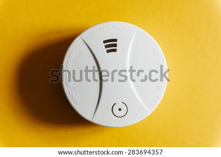 White smoke detector on yellow ceiling. - stock photo