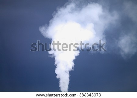 White smoke is coming out the chimney over the dramatic blue sky. - stock photo