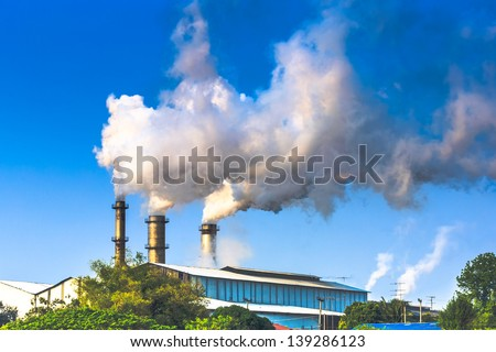 white smoking of three chimneys of a factory against a blue sky. - stock photo