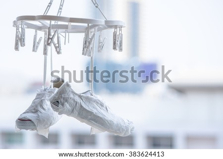 white sneakers hanging on the clothesline - stock photo