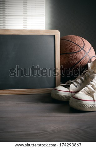 White sneakers with basketball and blank blackboard with copy space. - stock photo
