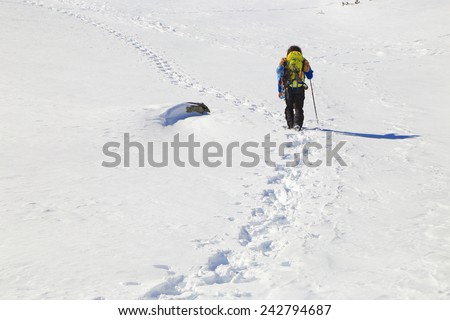 White snow field and distant backpacker leaving a foot step trail behind - stock photo