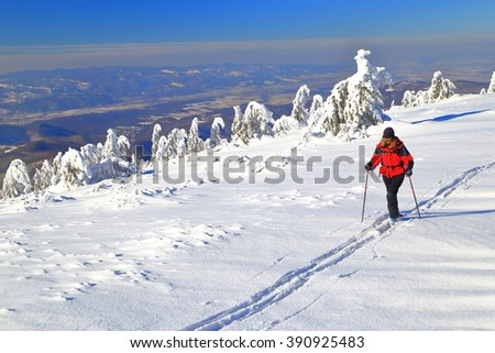 White snow field on the mountain and isolated woman climbing a trail on touring skis  - stock photo