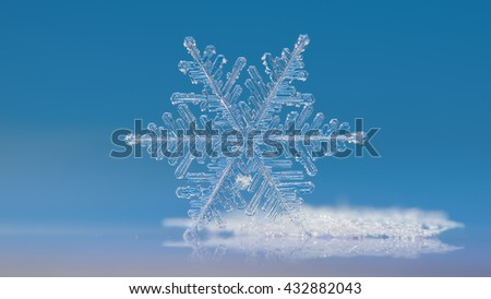 White snowflake on clear blue background: macro photo of real snow crystal, standing on it's edge and reflected in glass surface. This is very large and complex snowflake of fernlike dendrite type. - stock photo