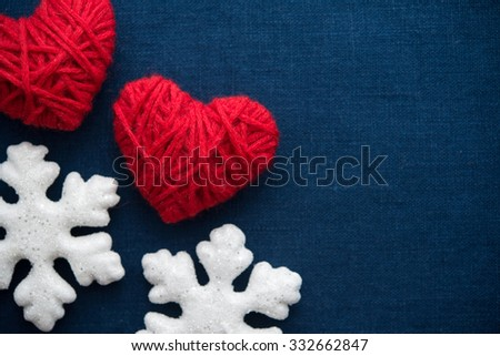 White snowflakes and red wool hearts on blue canvas background. Merry christmas card. Winter holidays. Xmas theme. Happy New Year. - stock photo