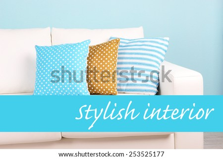 White sofa with colorful pillows on wall background, Stylish interior concept - stock photo