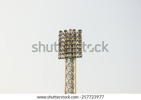 White spotlights pillar on blue sky background - stock photo