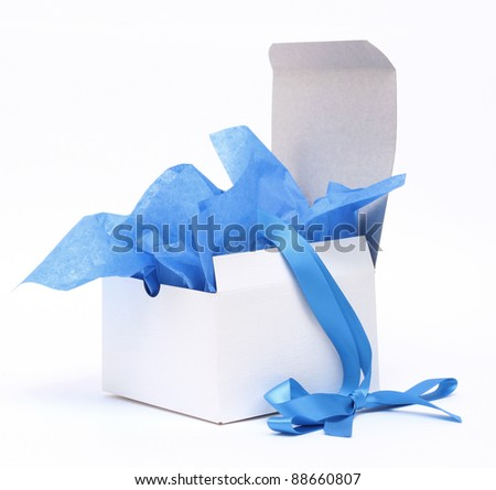 White square gift box with blue tissue and matching ribbon - stock photo