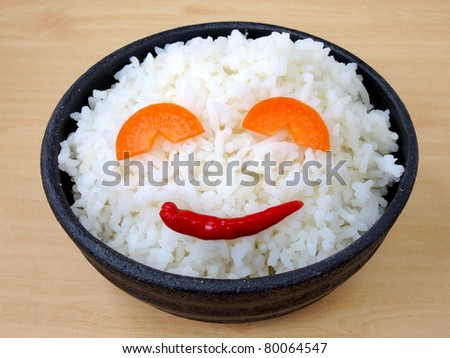 White steamed jasmine rice with fresh smiling chilli and carrot in black ceramic bowl - stock photo
