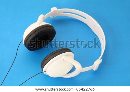 White Stereo Headset with black stars and wire on blue background - stock photo