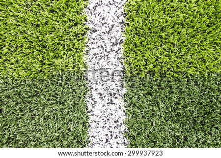 White stripe on the artificial grass light and dark green soccer field from top view  - stock photo