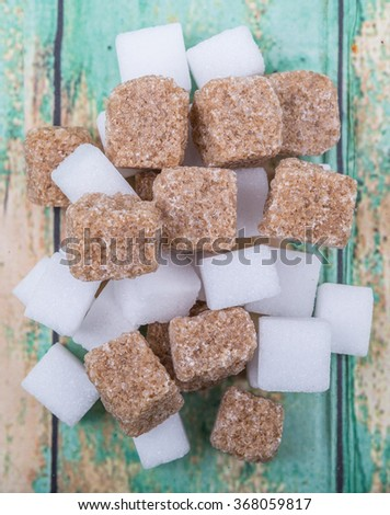 White sugar and brown sugar cane cube over wooden background - stock photo