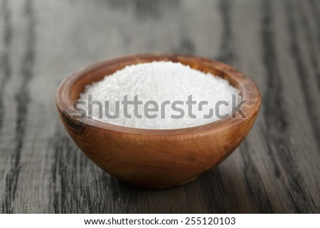White sugar in olive wood bowl - stock photo