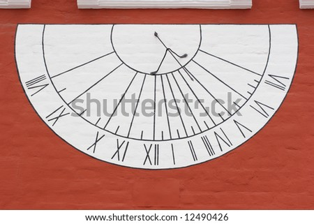 White sun-dial on red wall in Novodevichy Convent, Moscow, Russia - stock photo