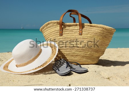 white sun hat and bag on the sunny beach - stock photo