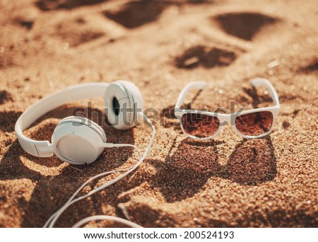 White sunglasses and headphones on sand - stock photo