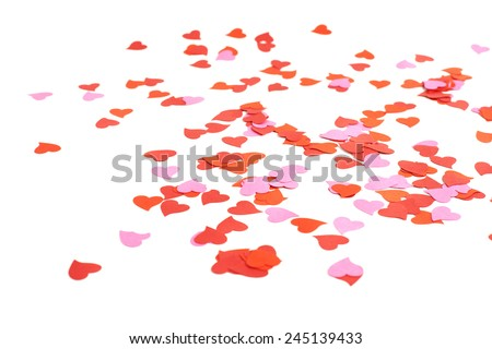 White surface covered with multiple red and pink heart shaped paper confetti as a romantic background composition - stock photo