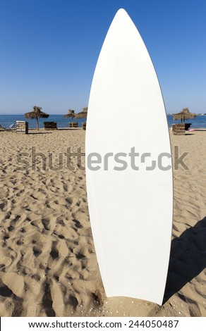 White surfboard is stuck in the sand. - stock photo