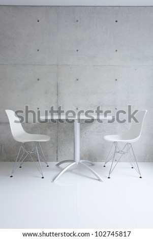 white table and chair against concrete wall - stock photo