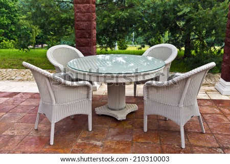 White table and chairs patio furniture in a garden's gazibo. - stock photo