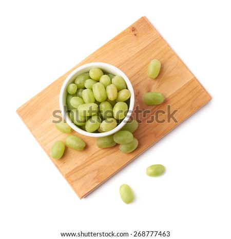 White table grapes in a ceramic bowl over the serving wooden board, composition isolated over the white background - stock photo