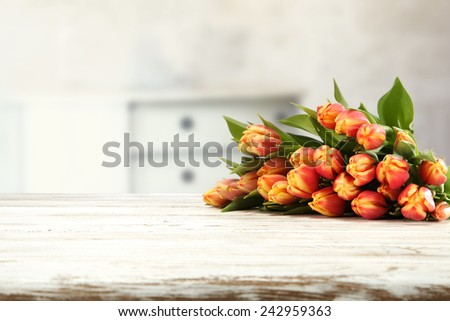 white table top and flowers of tulips and wall  - stock photo