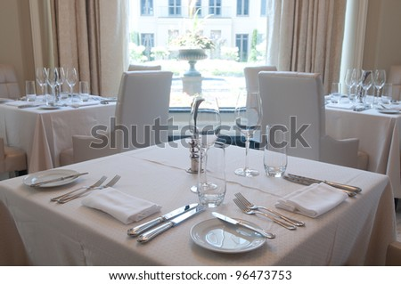 White tables with dinnerware and linens with a clean interior - stock photo